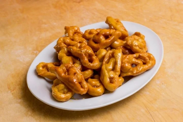 Honey coated Italian fritters called Caragnoli on a white platter.