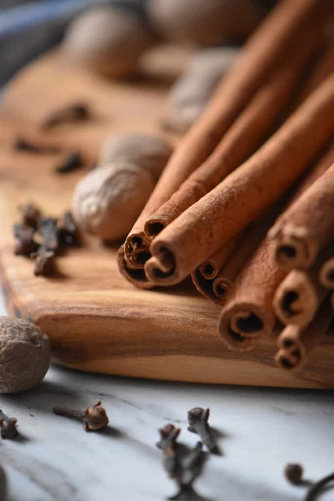 Long cinnamon stick on a wooden board, surrounded by whole nutmeg and cloves; the 3 ingredients required to make an allspice substitute.