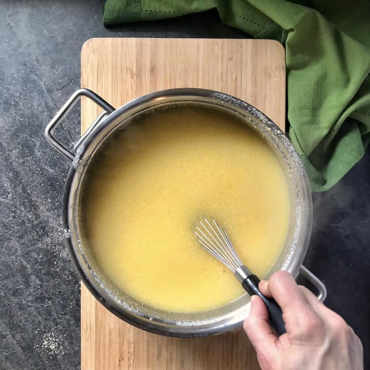 Whisking the cornmeal with the water in a large pot.