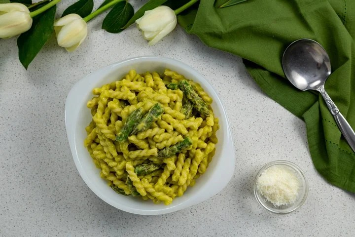 Creamy Asparagus Pasta in a white bowl, next to a small bowl of grated cheese, a green tea towel and tulips.