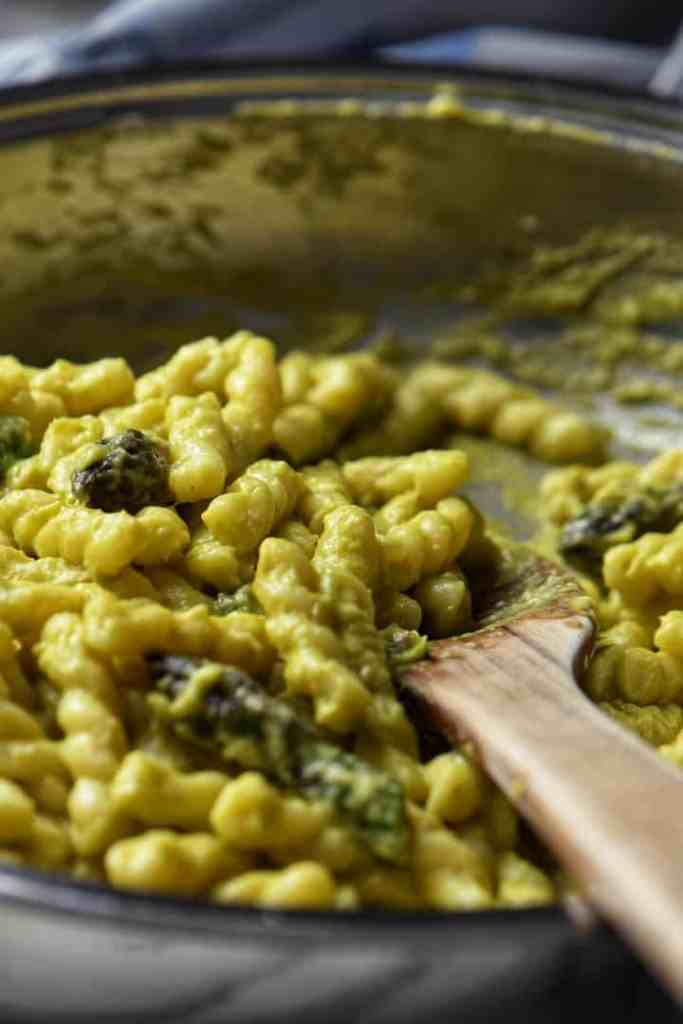 Gemelli pasta being tossed with the creamy asparagus sauce in a pan.