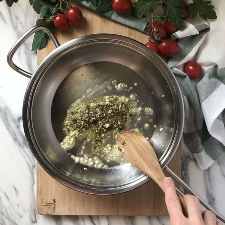 Traditional basil pesto is being added to sauteed garlic in a large pan.