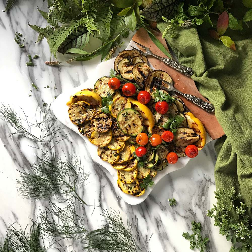An overhead photo of grilled vegetables on a white serving platter.