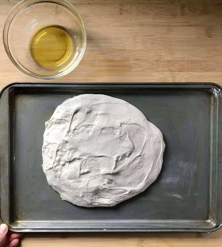 The wet dough of focaccia on a rimmed baking sheet.
