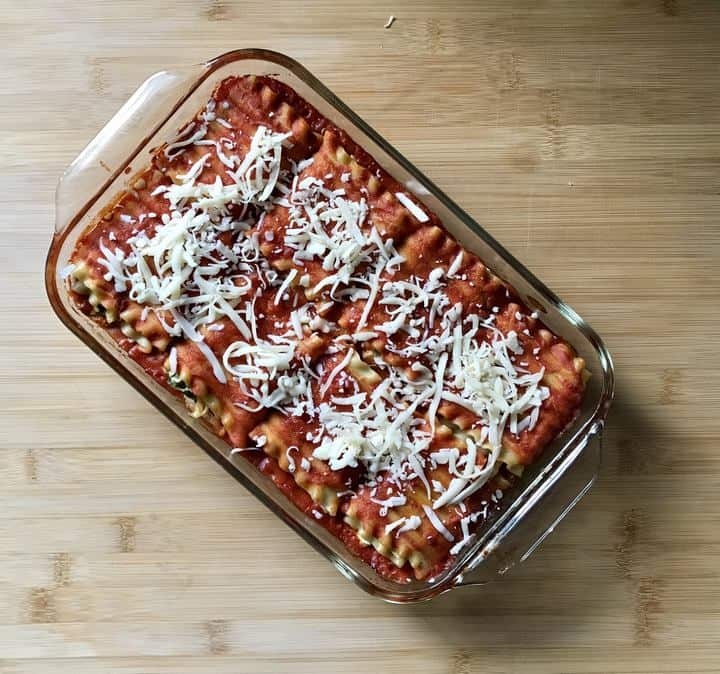 Grated mozzarella cheese sprinkled over the top of a baked lasagna roll ups.