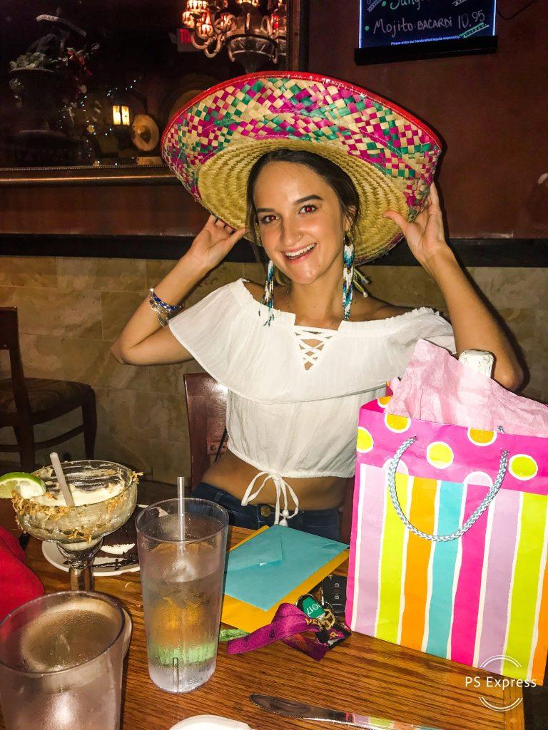 women-wearing-sombrero-smiling-margarita-gift-on-table