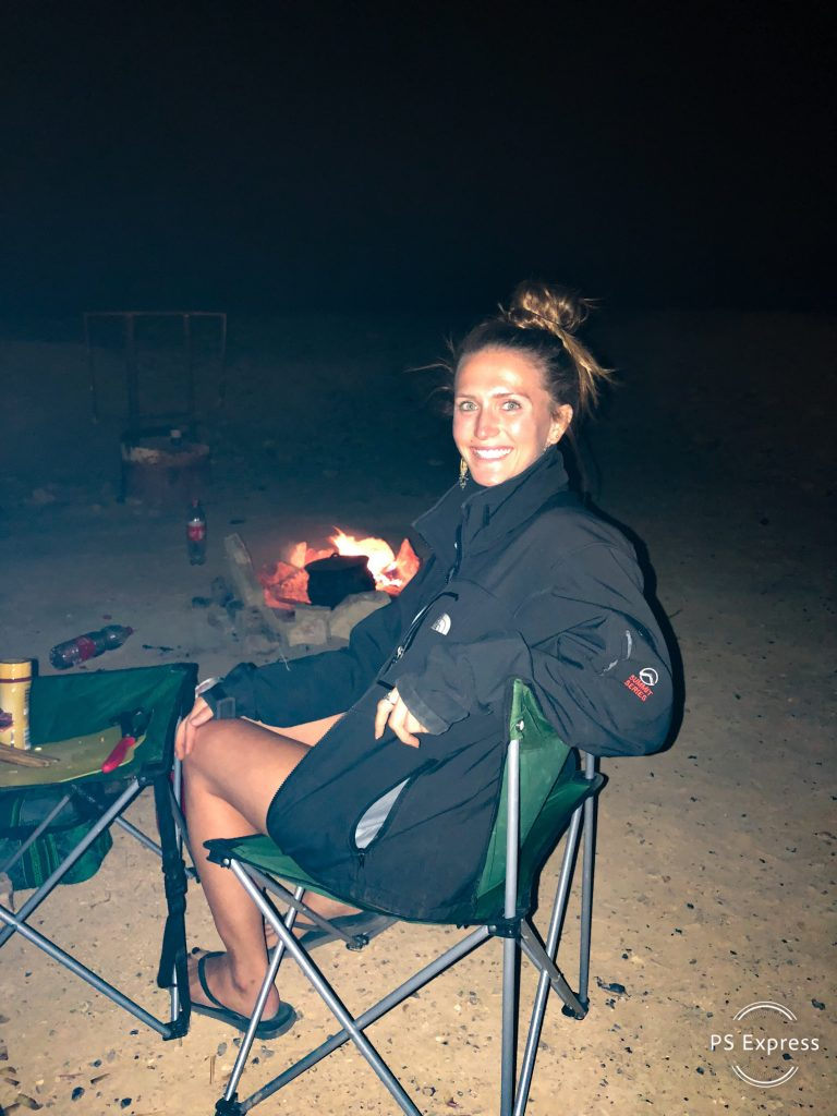 woman-smiling-sitting-in-camping-chair-nighttime