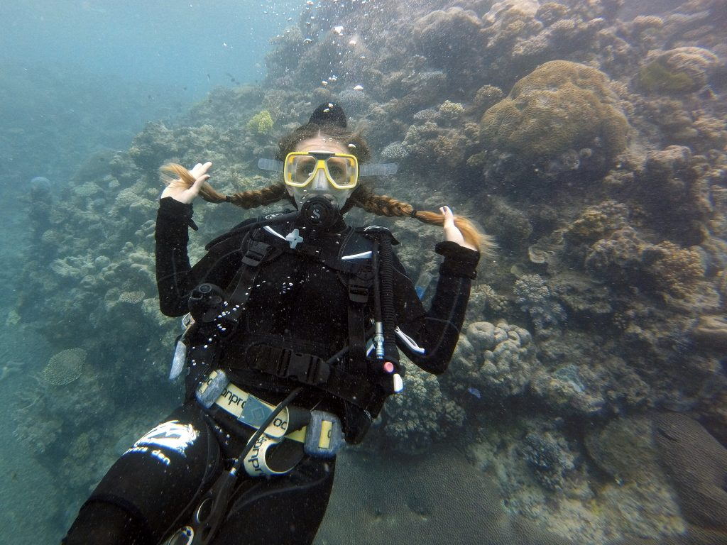 woman-scuba-diving-great-barrier-reef-holding-her-braids