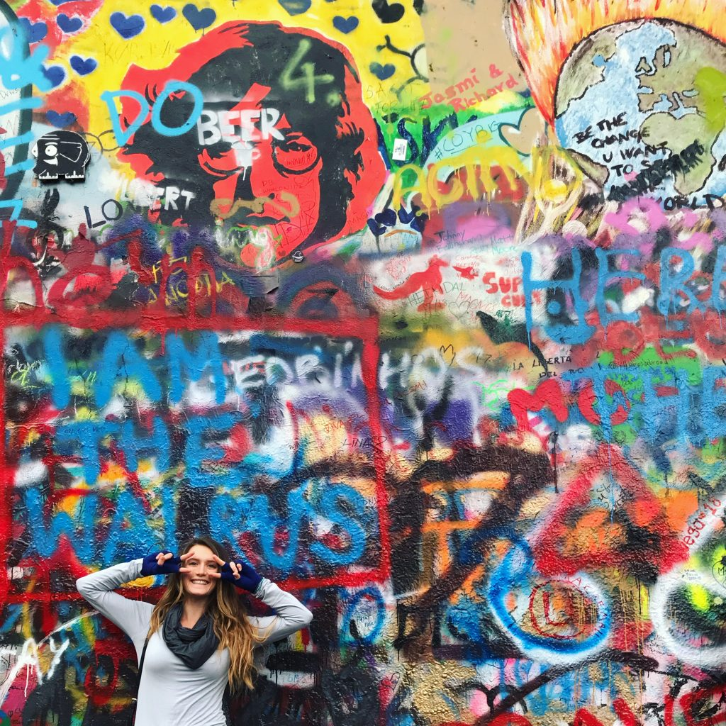 women-peace-signs-over-eyes-in-front-lenon-wall-prague