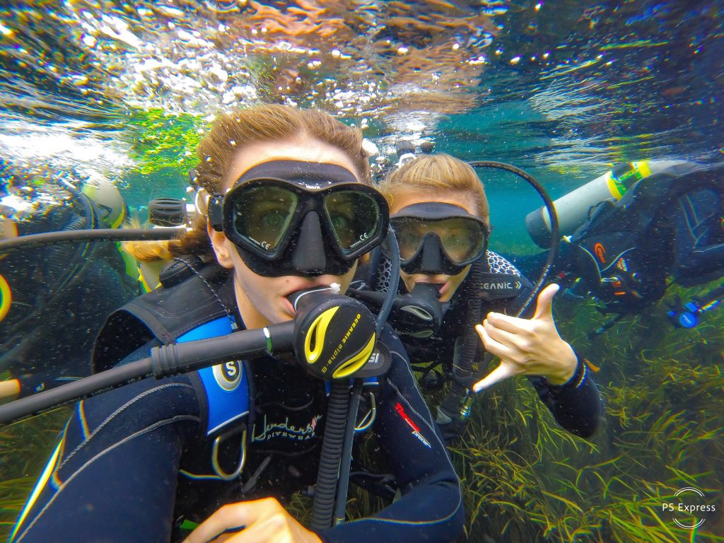 two-women-under-water-scuba-diving-shaka