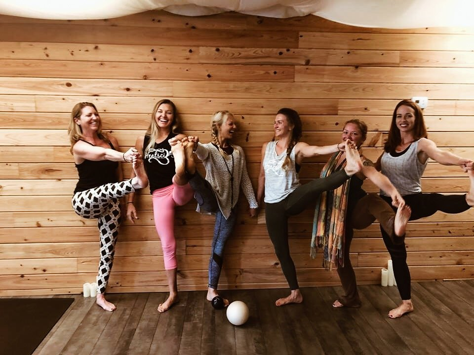 six-women-posing-yoga-against-wood-wall