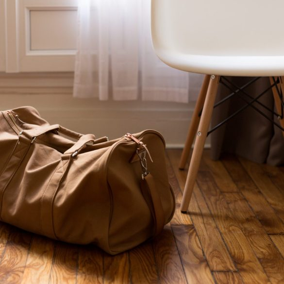 carry on packing list brown duffel back next to chair