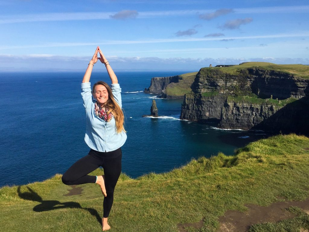 woman standing yoga pose cliffs of moher tips for finding cheap flights