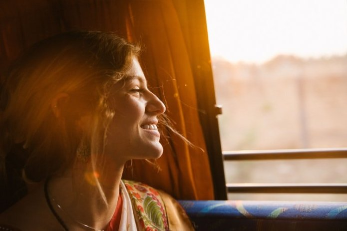 woman staring out train window at sunset