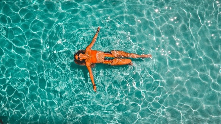 woman floating in pool in orange bikini