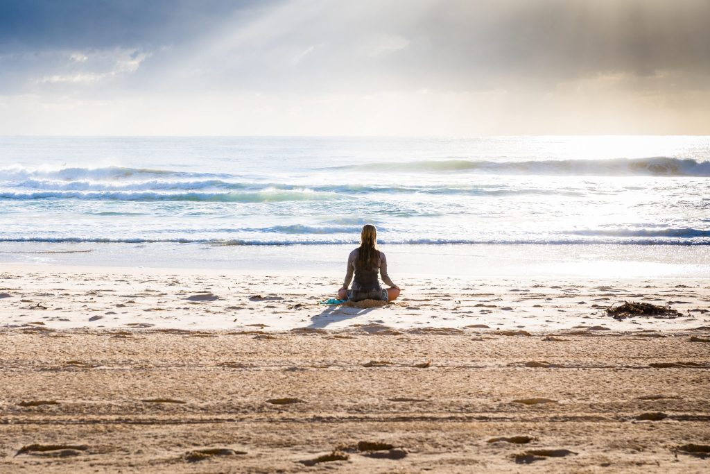 meditating on beach solo travel