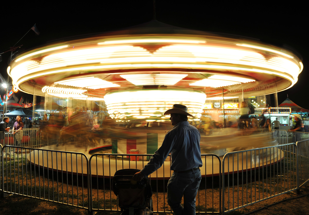 Cody Wright of Corsica, South Dakota, waits for his family as they ride the carousel in the carnival Saturday night at the Sheridan County Fairgrounds.