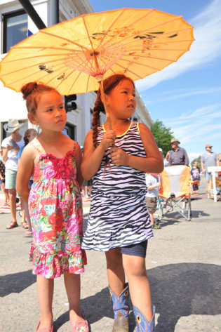 Three-year-old Bonita Limpy, left, and Diana Old Elk, 5, watch from the shade of an umbrella during the 2014 Sheridan WYO Rodeo Parade Friday morning on Main Street.