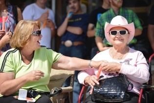 Gayla Merman, left, shares a laugh with her mother Arlene Colins after struggling to open a frozen popsicle treat during the 2014 Sheridan WYO Rodeo Parade Friday morning on Main Street.