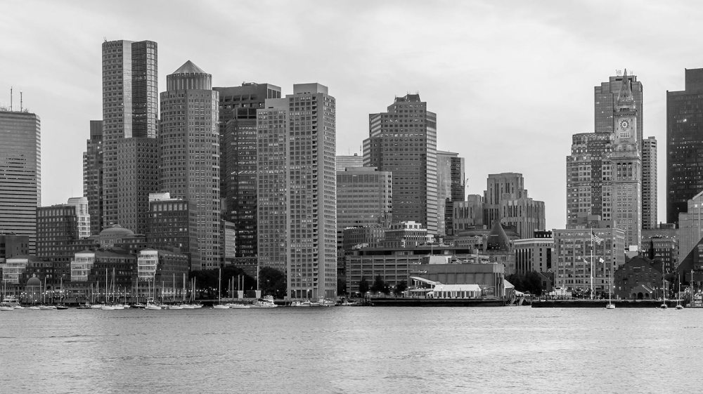 Black and white photo of downtown Boston with skyscrapers overlooking Boston Harbor