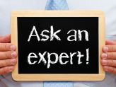 "a man holding a small chalkboard that has "" Ask an expert!"" on it"