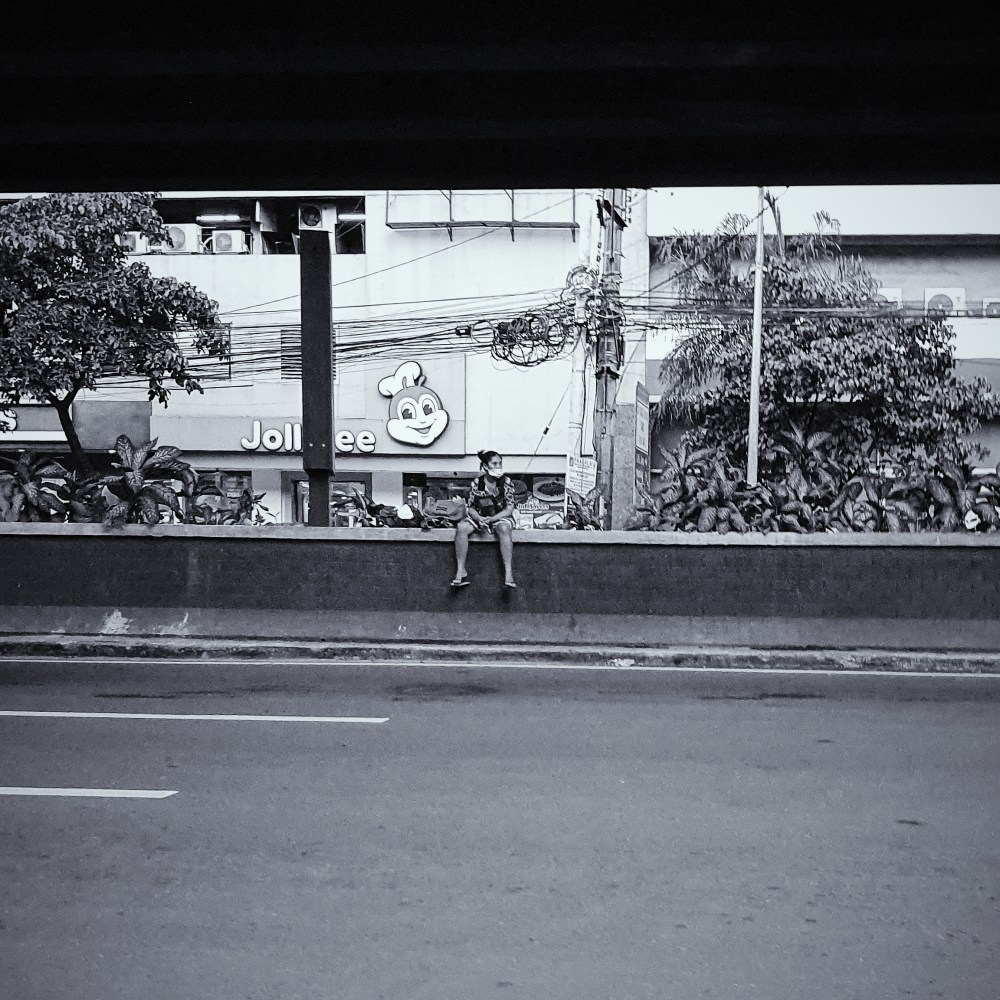 Street Photography in Manila, Philippines - Woman Sitting on an Barrier