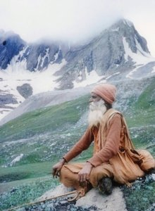 bearded man meditating in mountains