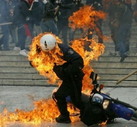 A policeman is seen in flames as he trie
