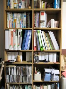 僕のデスク反対側の棚。最近使った本と、その辺に転がっていた本がとりあえず入っています。上から 3 段目にある説明書ファイルもお勧めの収納アイテム。一番下の段にはケーブル収納ファイルと、小物収納ファイルもあります。これらもお勧め!