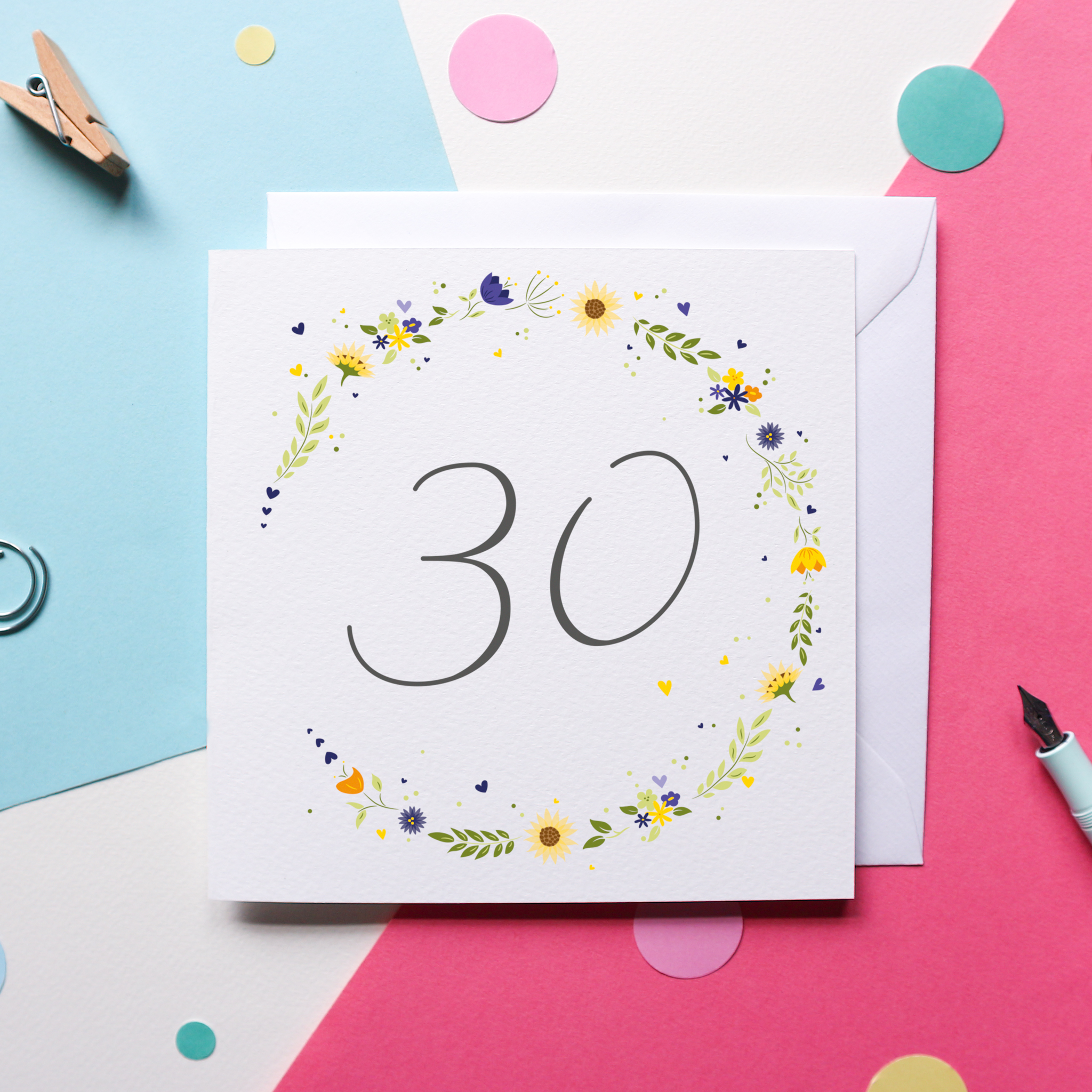 """A charming Birthday card that reads """"30"""" in hand drawn lettering in grey text against a white background, surrounded by a circle of Yellow and blue flowers. The card sits against a white envelope and a blue and pink background with bright confetti, a pen and some paper clips."""