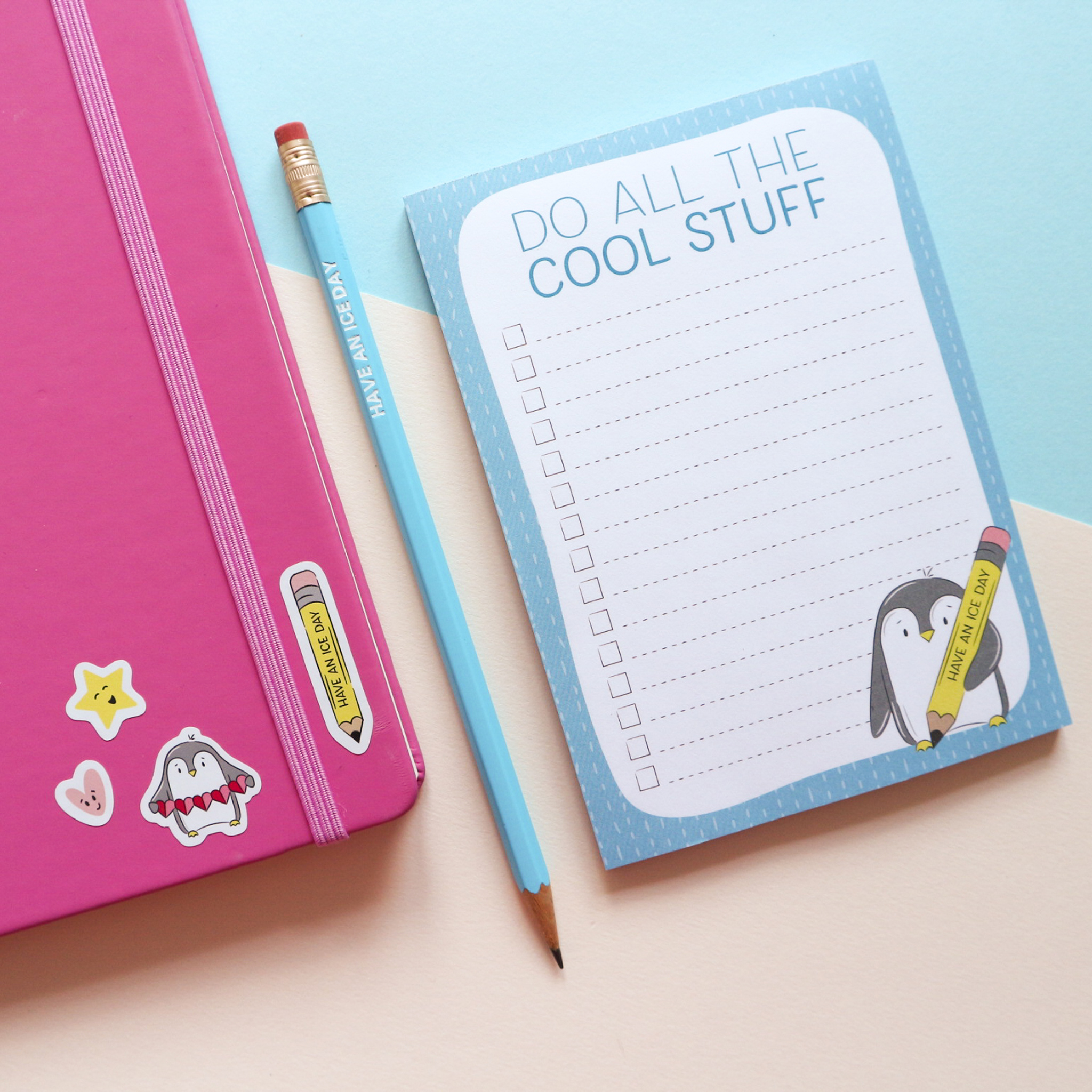 """""""Do All the Cool Things"""" To-Do List Notepad with an illustration of a penguin holding a pencil that reads """"Have an ice day"""" and blue pencil (which comes in a set) that reads """"Have an ice day"""" styled with a pink notepad and matching stickers, on a white and blue background."""