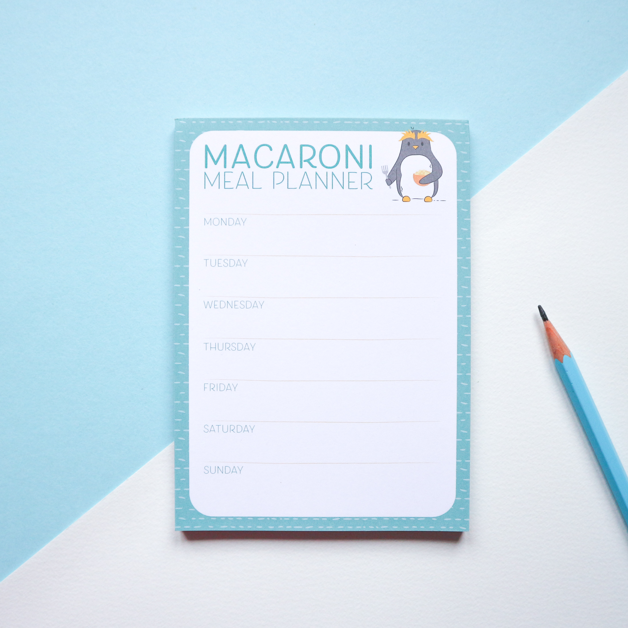 Macaroni Meal Planner Notepad with an illustration of a Penguin eating a bowl of macaroni. The notepad is styled with a blue pencil and sitting against a blue and white background.