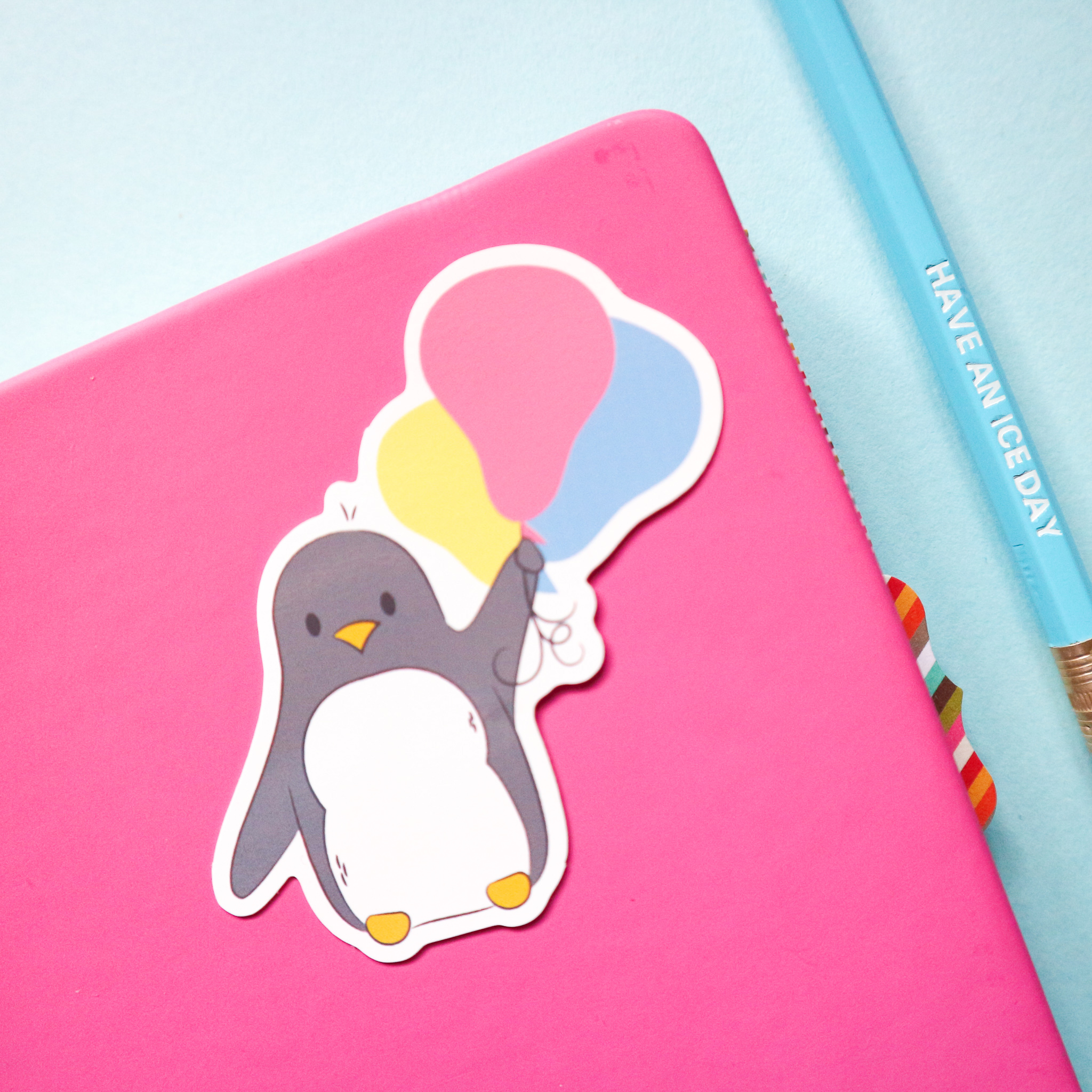 "an illustrated sticker of a cute penguin floating away with a bunch of balloons. The sticker is stuck on a pink notebook and styled with my ""Have an ice day"" pencil."