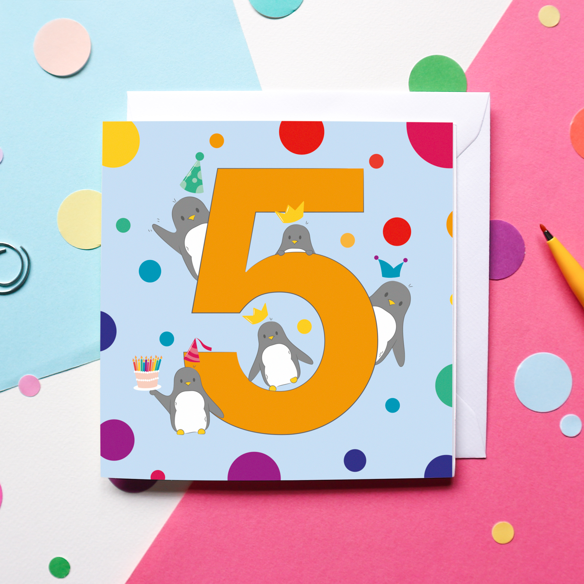 A Penguin-themed 5th Birthday Card on a colourful background surrounded by confetti and a pen.