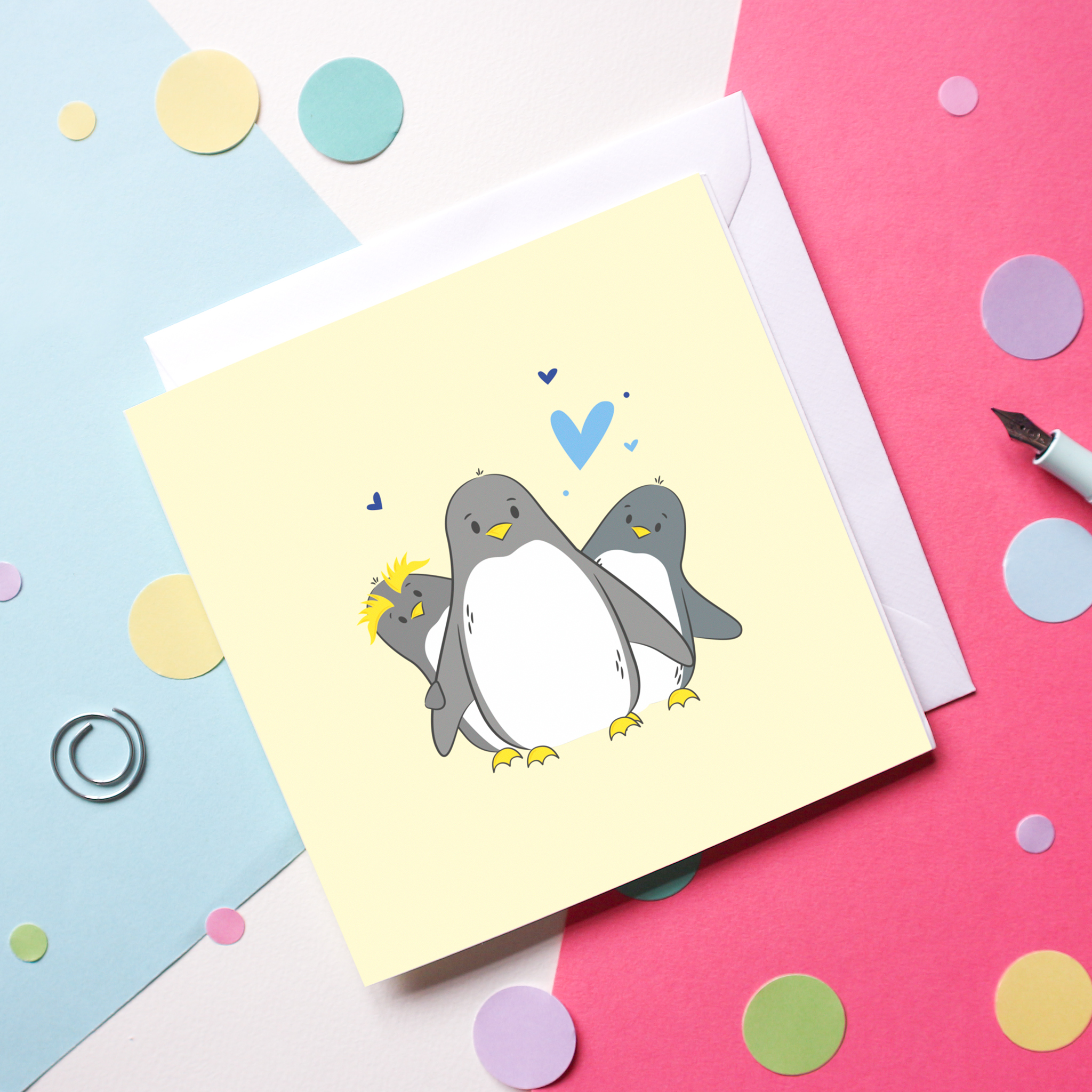 An image of an illustrated penguin mother's day card. The card shows an adult penguin with 2 smaller penguins either side, surrounded by blue hearts, set on a pale yellow background. The card is set on a colourful background with colourful confetti.