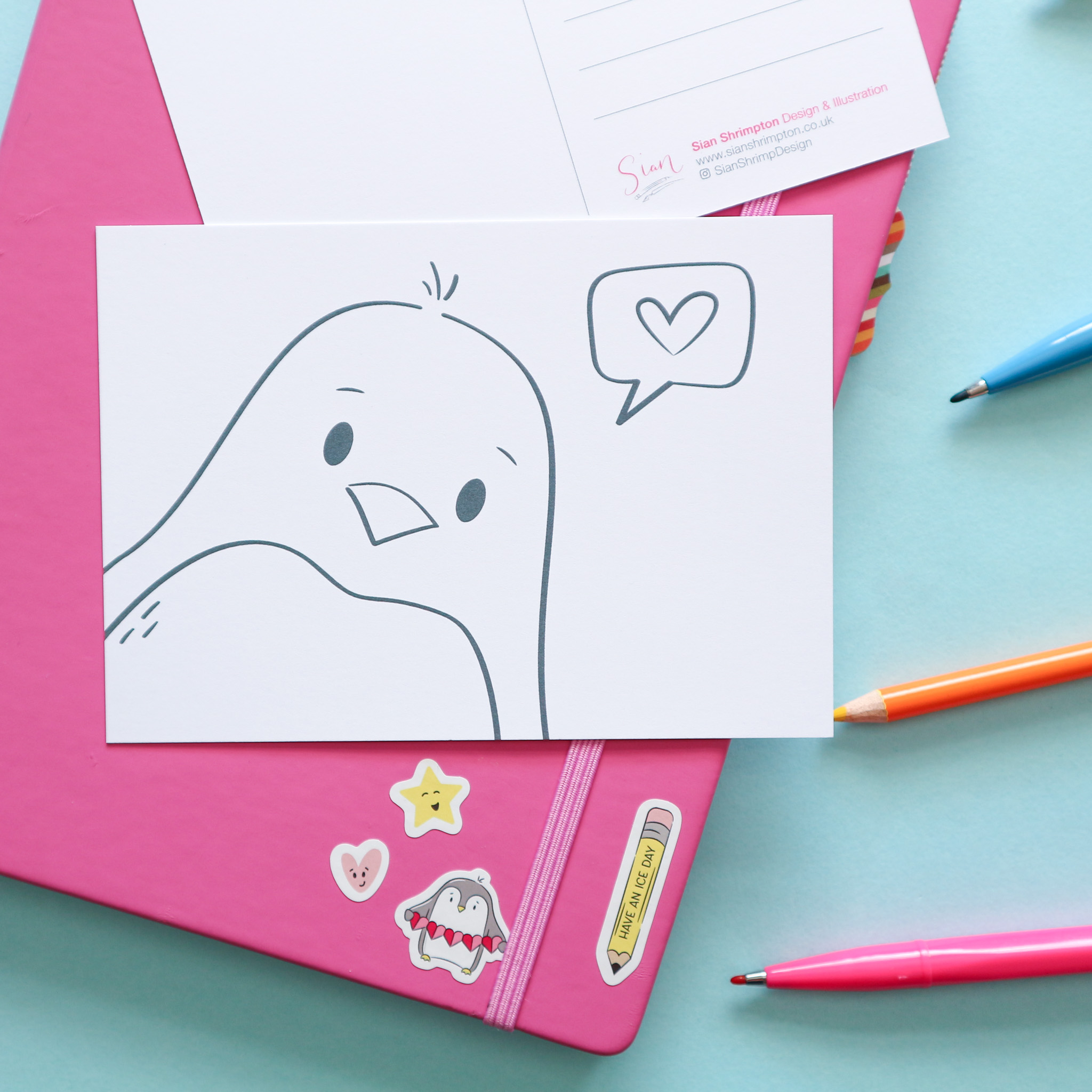 Postcard design showing an illustration which is un-coloured, to be coloured in by you or the recipient. This design shows a penguin with a speech bubble with a heart inside.