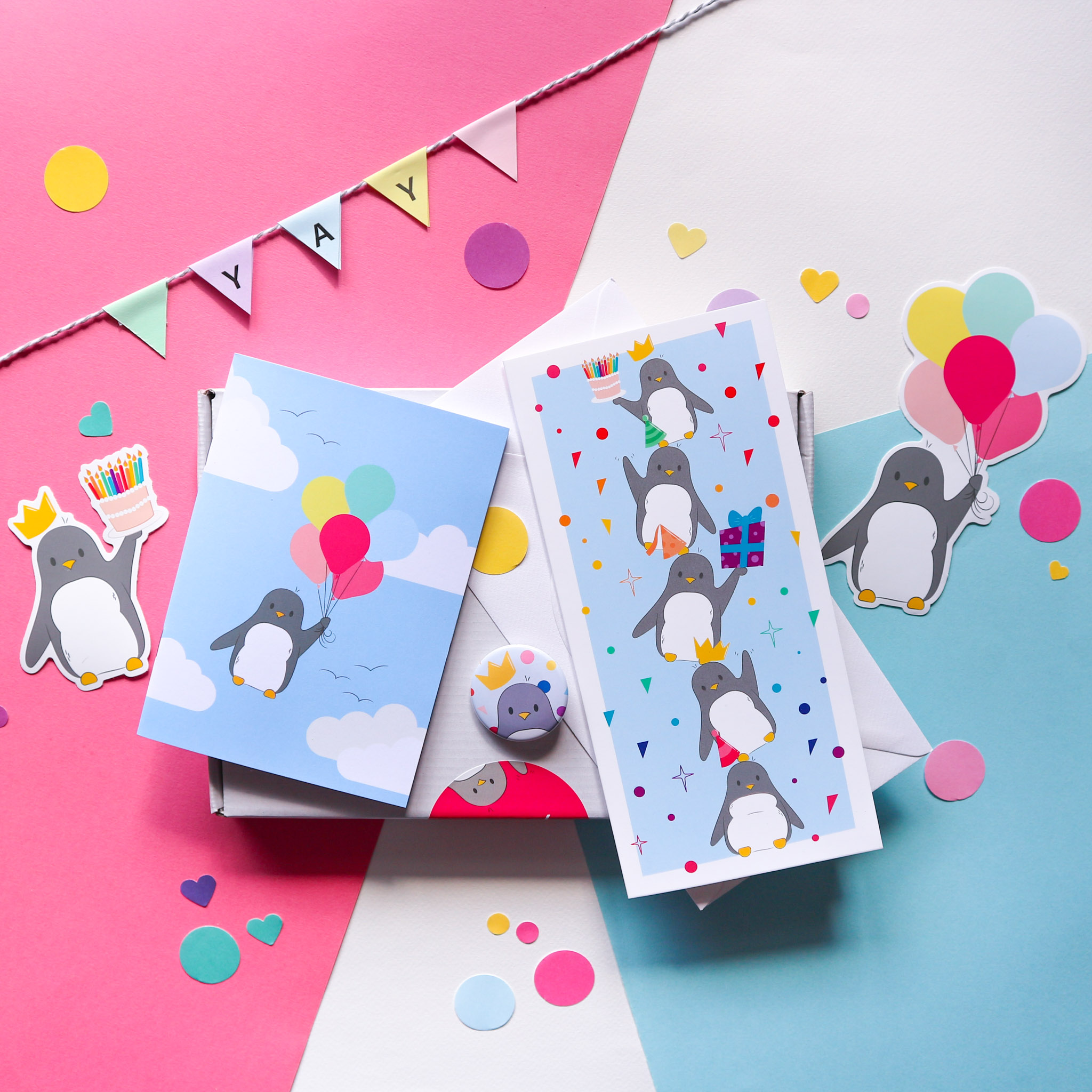 "Flatlay photograph of all the products in the birthday bundle box, two penguin birthday stickers (one holding a birthday cake, the other holding balloons), a little notebook with a penguin holding a bunch of balloons on the front, a string of paper saying ""yay,"" a birthday card and a penguin birthday badge."