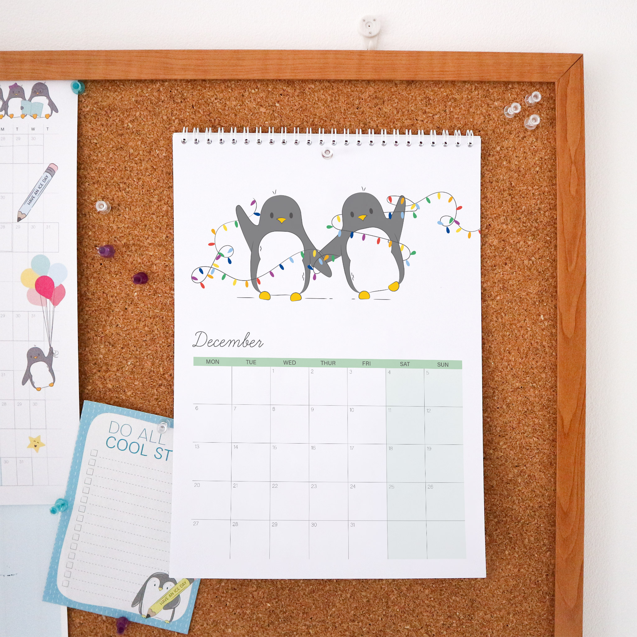The December page of the Penguin Calendar is an illustration of 2 penguins all tangled up in some Christmas lights. This Calendar is wire bound A4 and is styled against a cork board background.