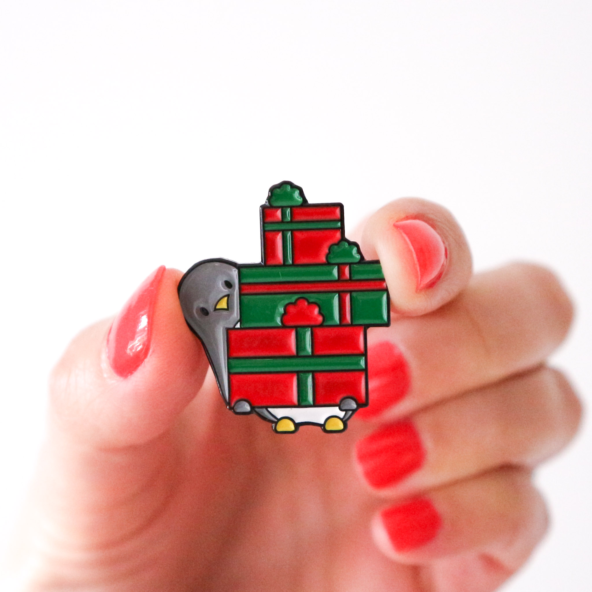A photo of a hand, with red painted fingernails holding the Penguin Christmas Pin which is penguin holding a large stack of red and green gifts against a white background.