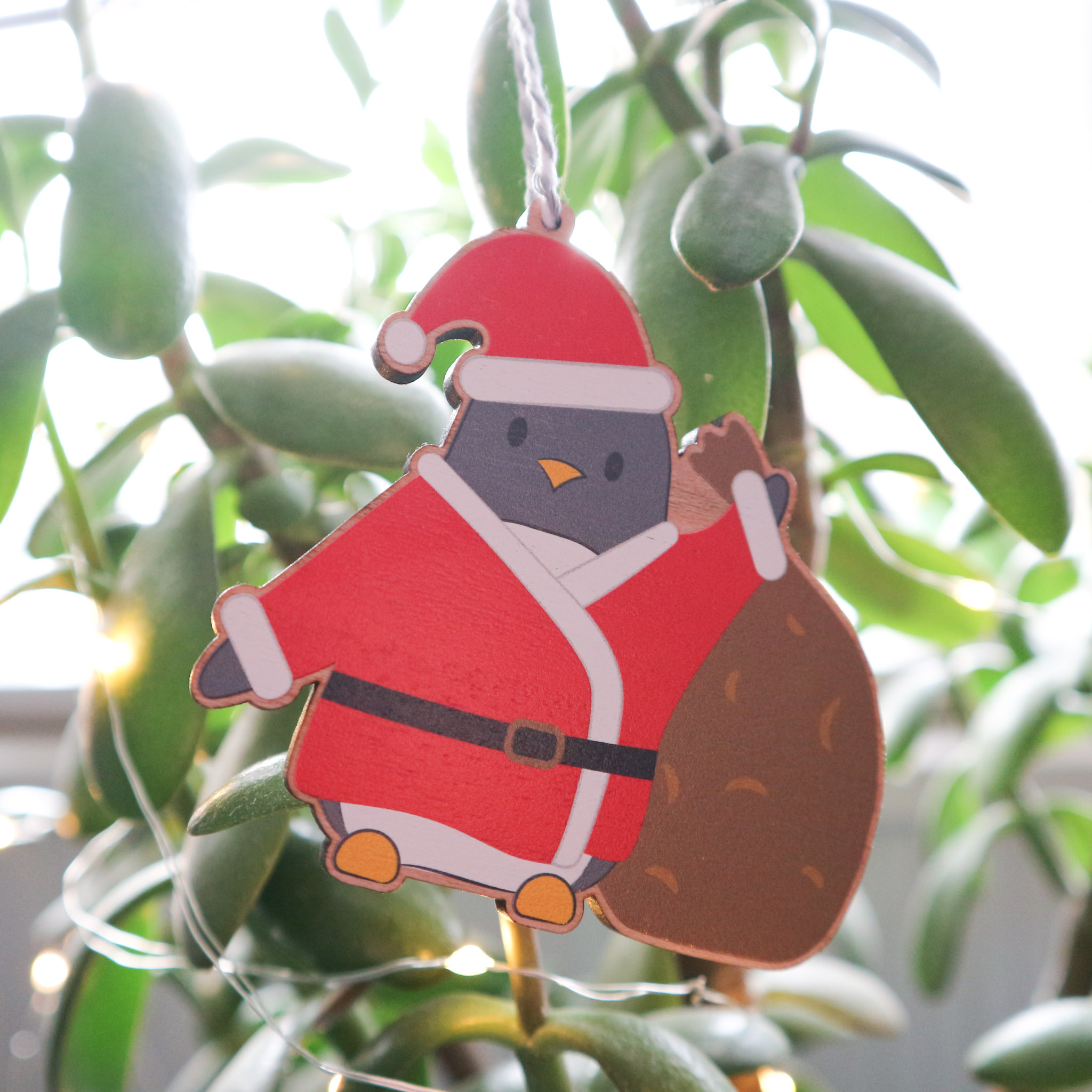 An illustrated wooden Christmas decoration is hanging on a leafy green plant surrounded by fairy lights. The illustration is of a cute penguin dressed as Father Christmas and is holding a sack full of gifts.