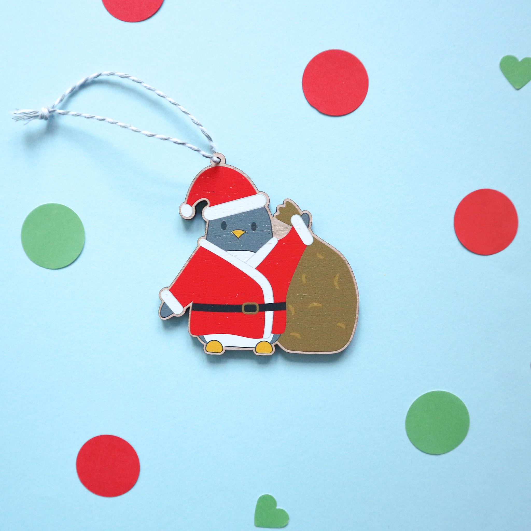An illustrated wooden Christmas decoration is laying flat against a blue background and surrounded by red and green confetti. The illustration is of a cute penguin dressed as Father Christmas and is holding a sack full of gifts.