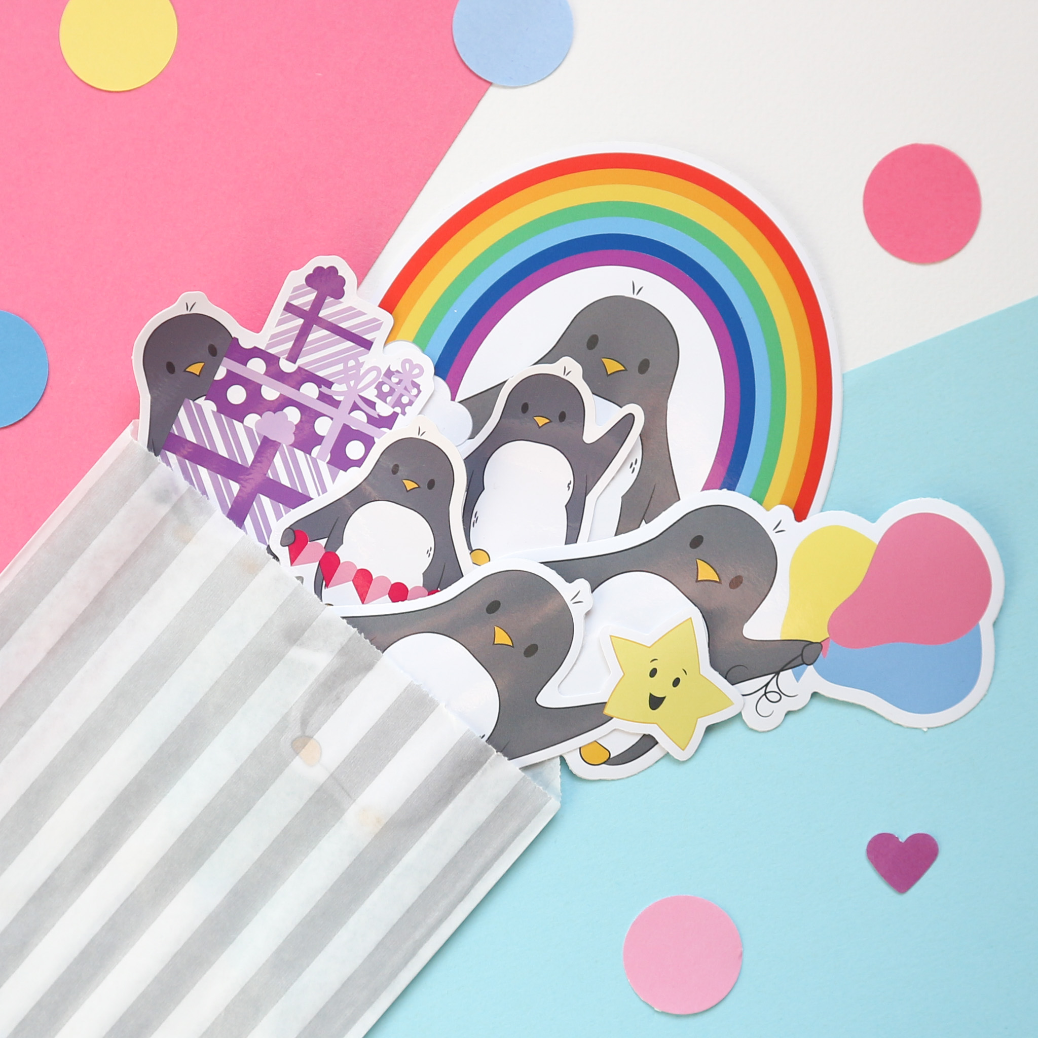 A group of colourful and cute penguin stickers are peeking out of a striped paper envelope. They are sitting against a pink, white and blue background surrounded by colourful confetti.