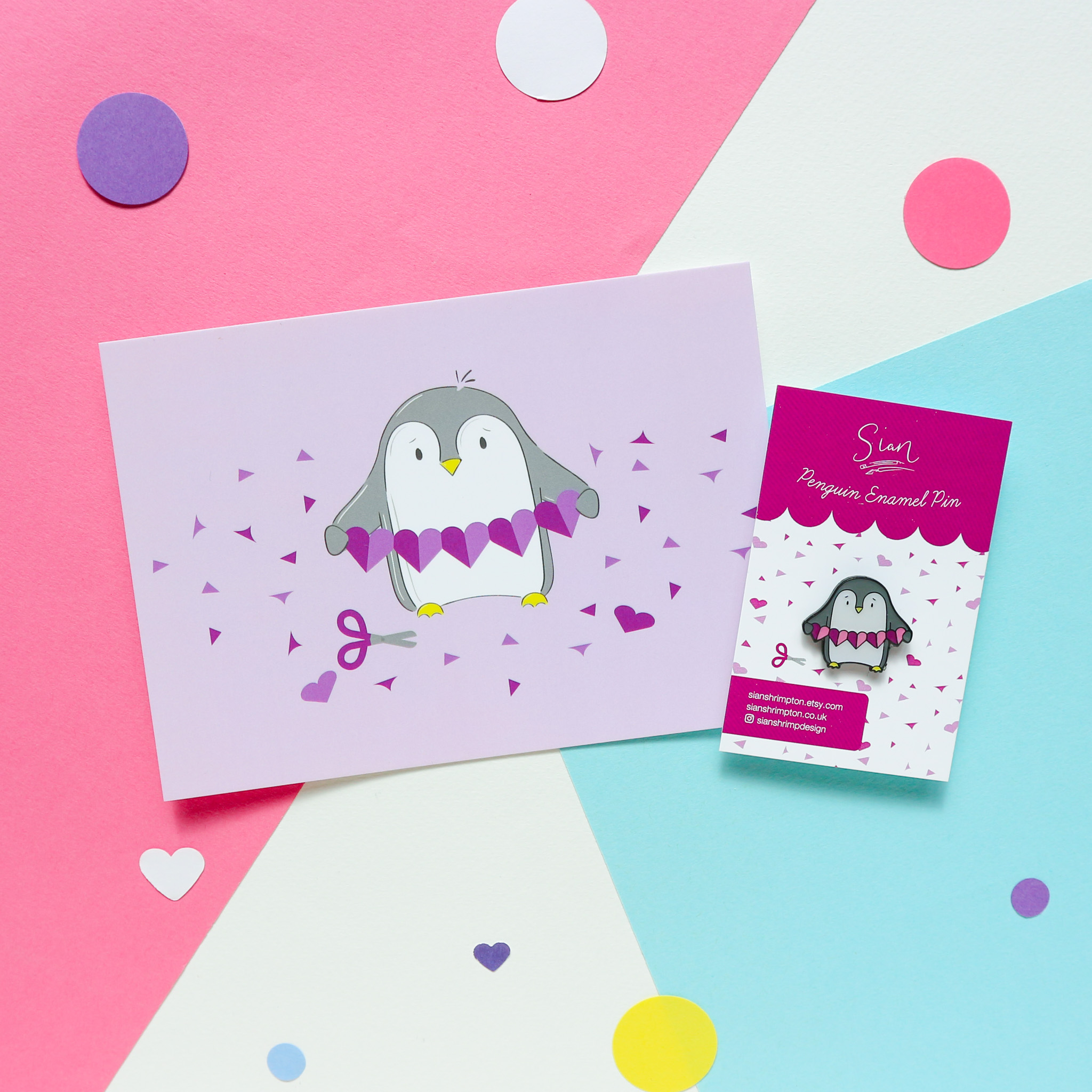 Penguin Enamel Pin holding a purple heart garland and a matching postcard, all set against a colourful background.