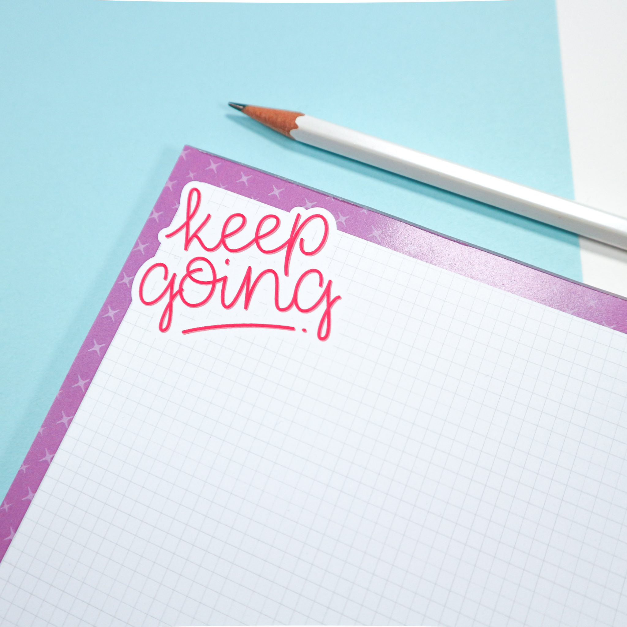 """A photo of an A5 deskpad, which has a purple border, grid paper and reads """"keep going"""" in pink hand drawn lettering in the top corner. Deskpad sits against a blue and white background styled with a white pencil."""