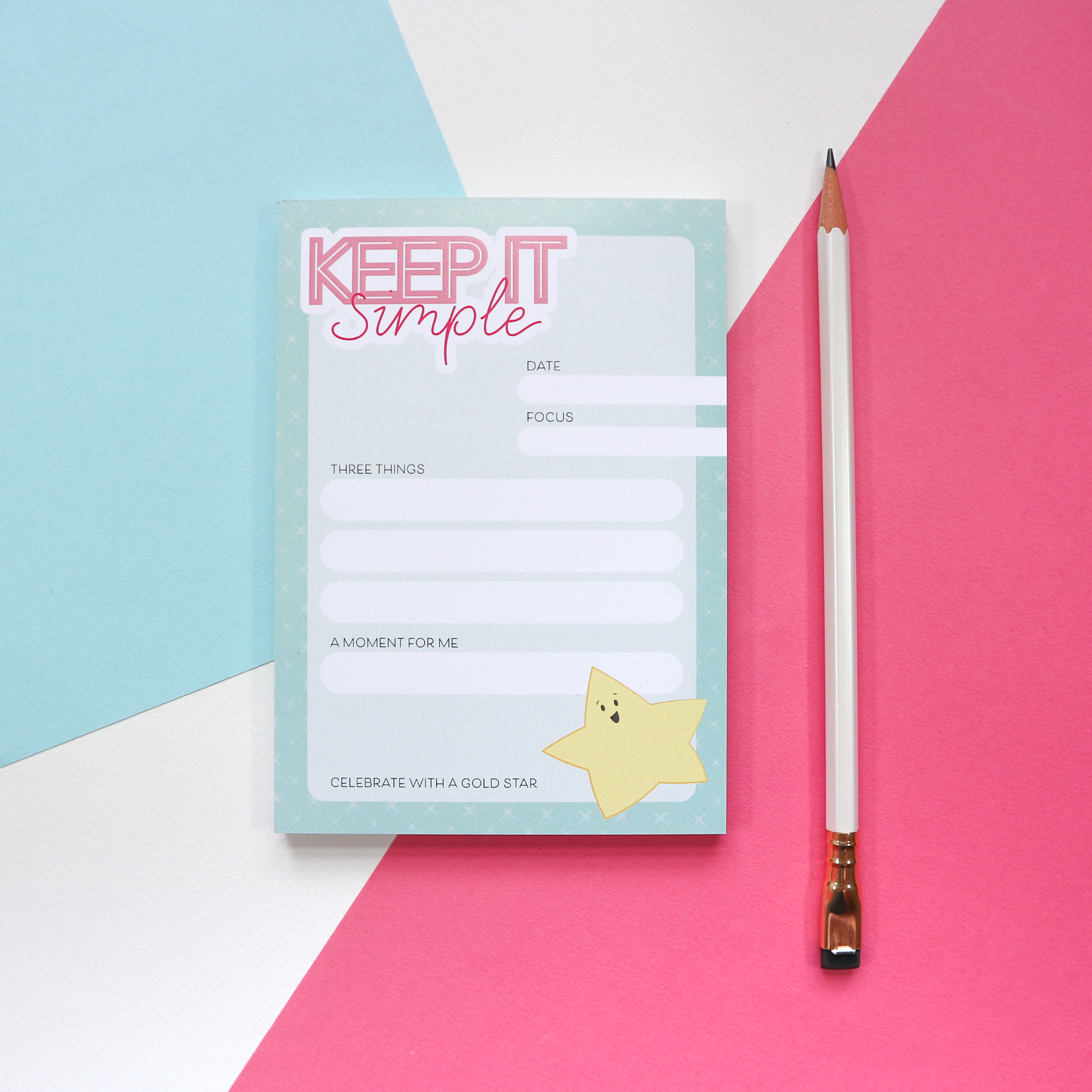 """A photo of an A6 notepad design with a mint green background and the words """"keep it simple"""" in the top corner. There is space for the date, focus for the day/week, then 3 to-list list items, """"a moment for me"""" and a smiley gold star at the bottom to celebrate your win(s) for the day/week. The notepad sits against a pink, white and blue background and is styled with a pencil."""