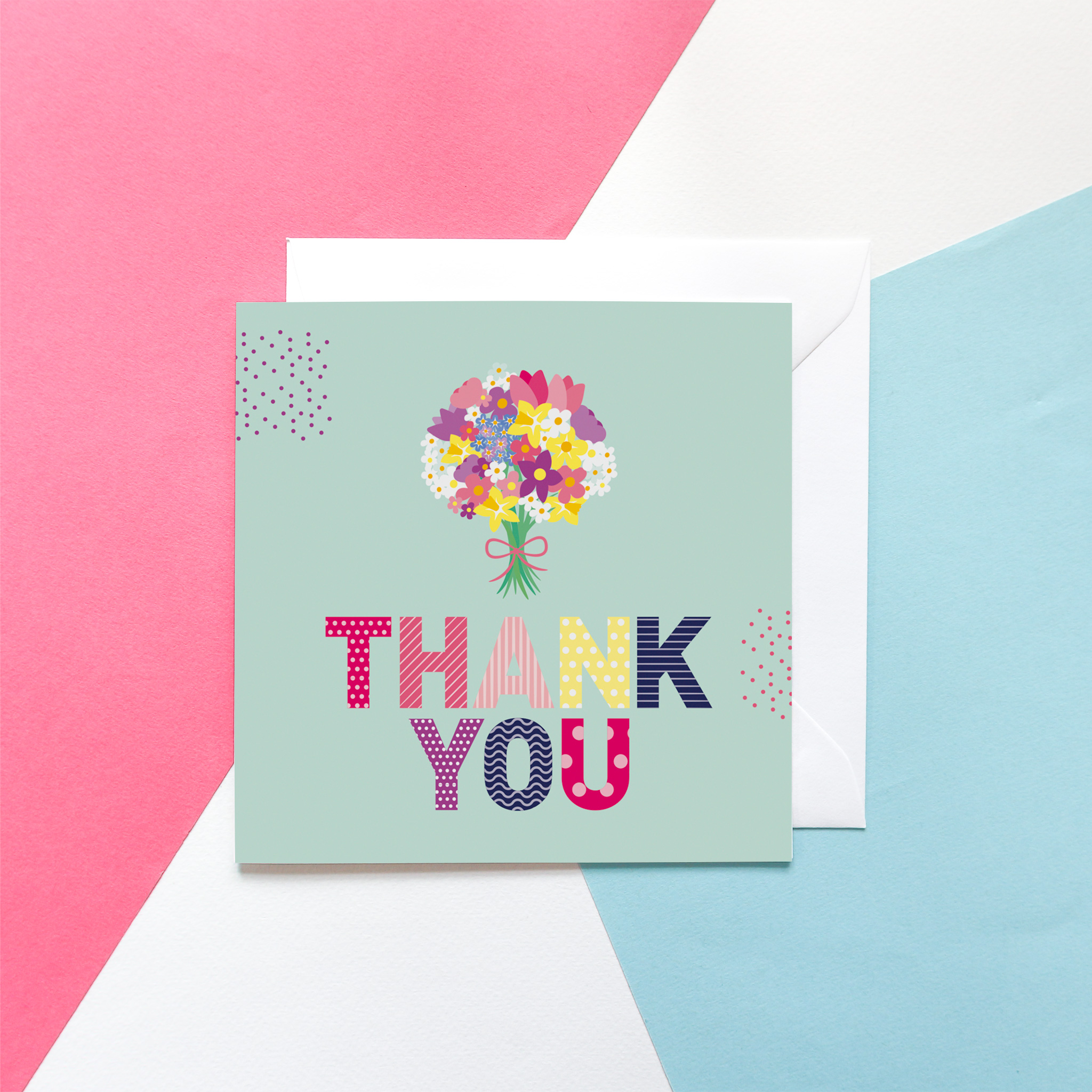"""Graphic """"Thank you"""" card design with patterned, colourful letters and a colourful bunch of flowers above the lettering, against a mint green background. The card is set against a pink, blue and white background."""