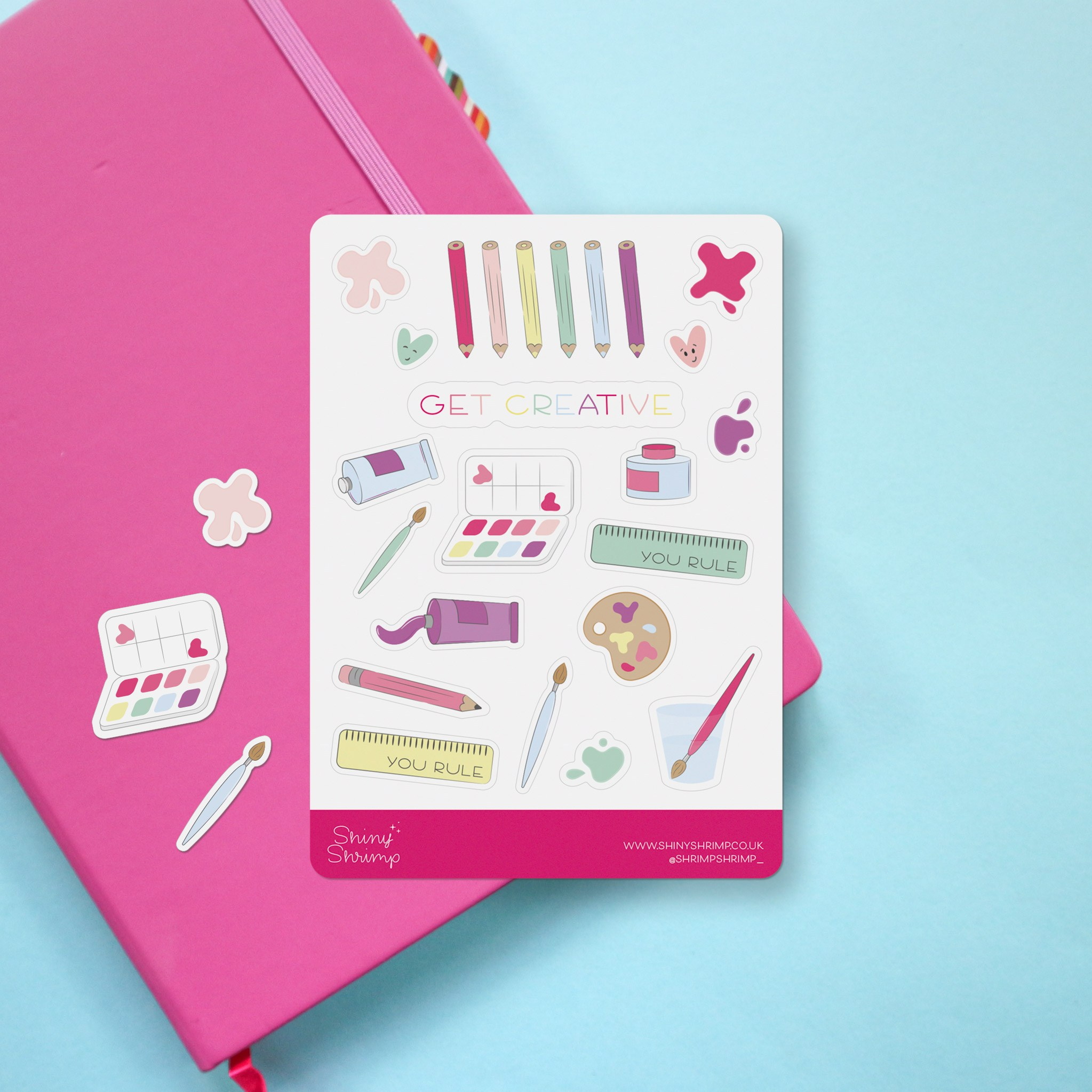 """Photo of a planner sticker sheet showing all kinds of colourful art and craft supplies. To the centre of the sheet is the words """"get creative"""" in a hand lettered style."""