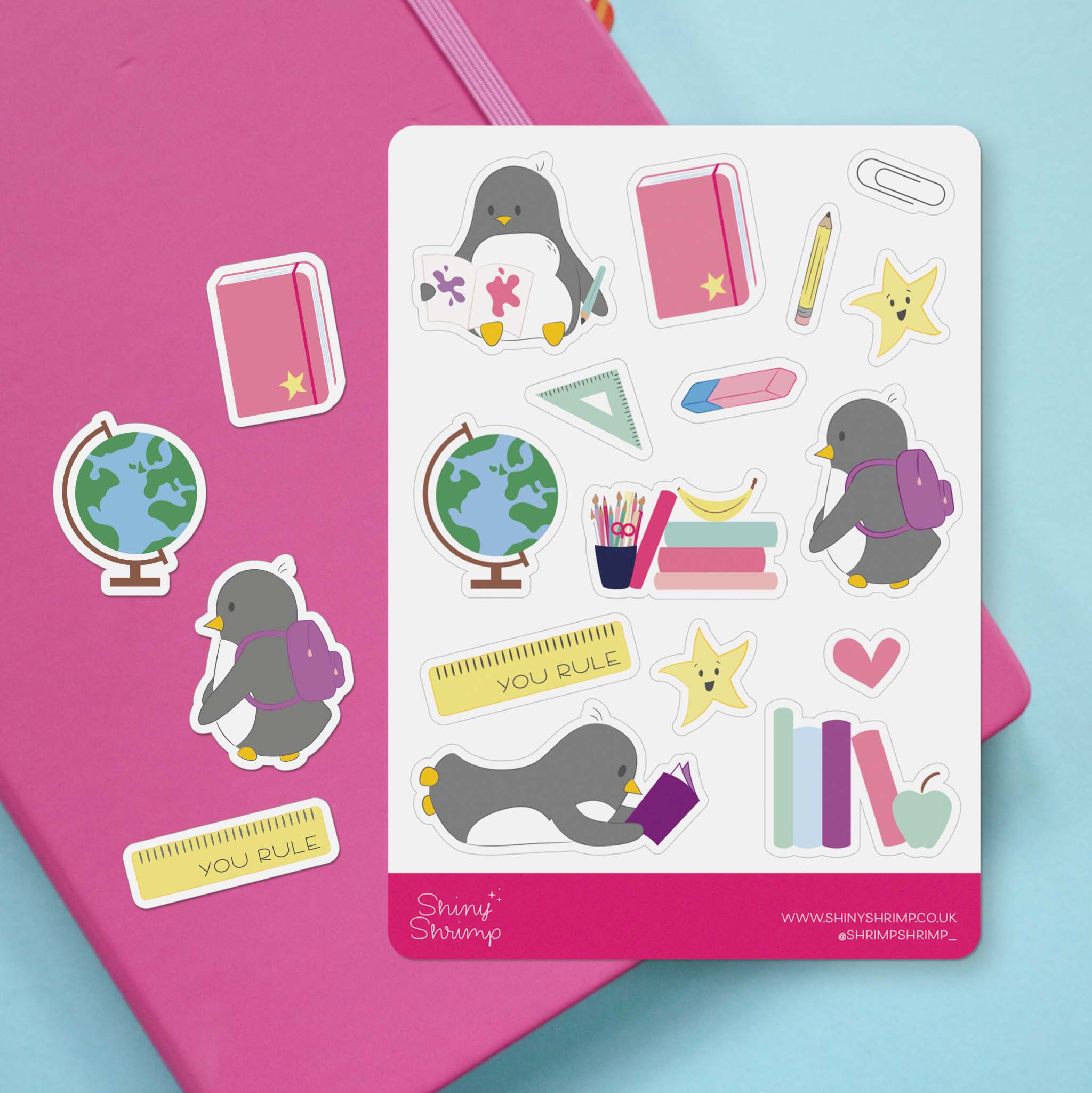 A back to school themed penguin sticker sheet with cute illustrations around the theme of back to school. It sits against a pink and blue background.