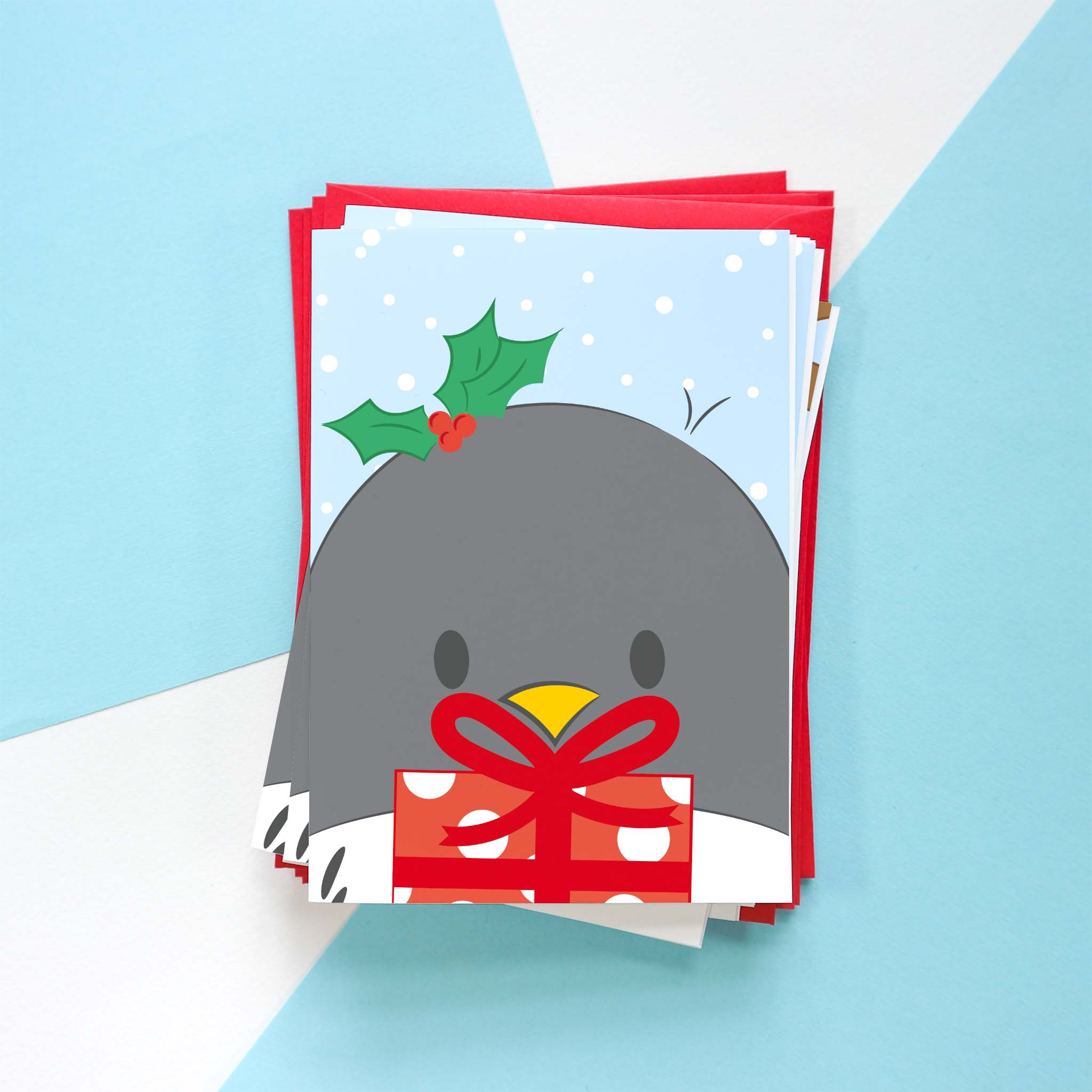 A photo of a Penguin Christmas card design. This design is of Penguin holding a red gift with a big red ribbon and holly on their head.
