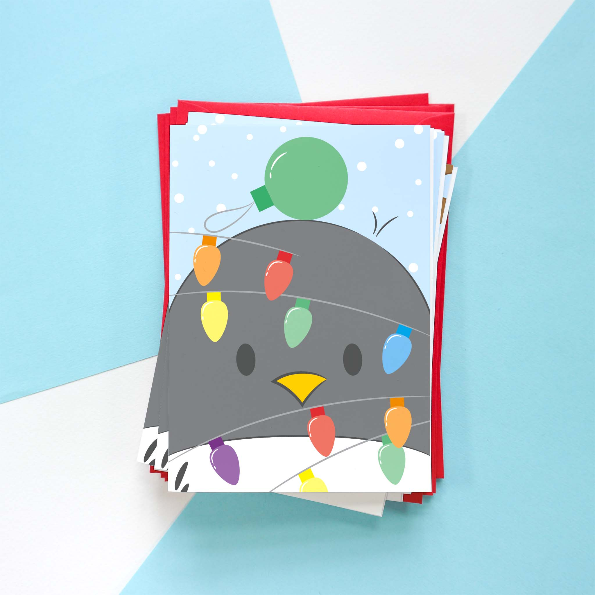 A photo of a Penguin Christmas card design. This design is of Penguin tangled up in colourful fairy lights with a green bauble on their head.
